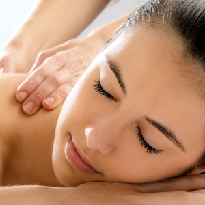 Close up portrait of young woman relaxing in spa.Therapist doing back massage on girl in background.